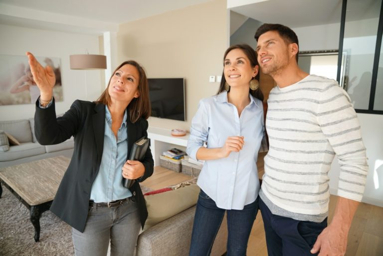 Real estate agent touring a couple inside a house