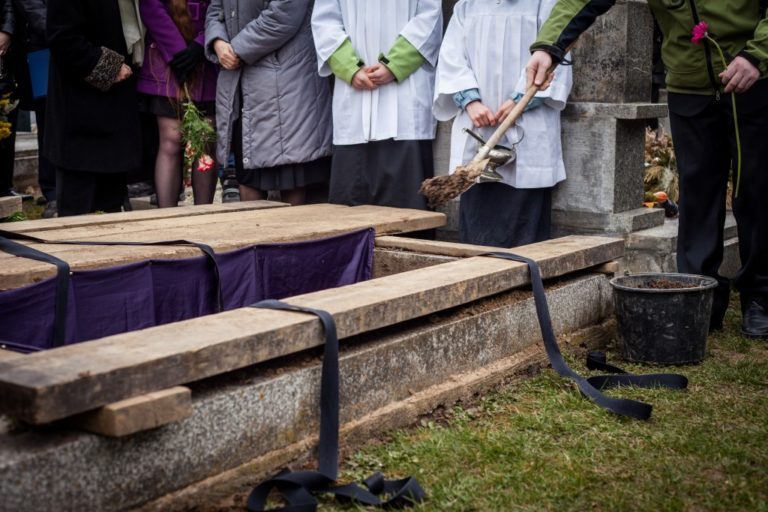 burying a coffin at a cemetery