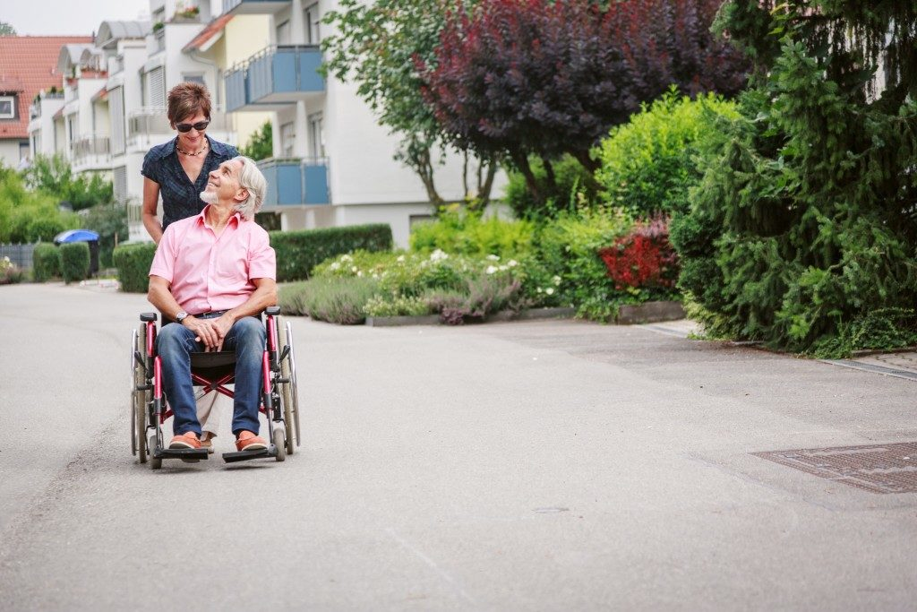 senior man in wheel chair with his daughter getting fresh air