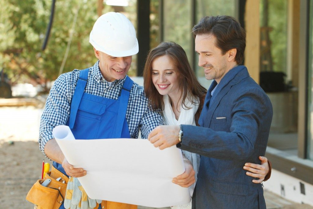 couple looking at their house blueprint with the contractor