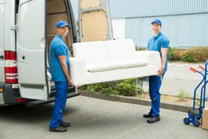 Two workers putting furniture down from truck