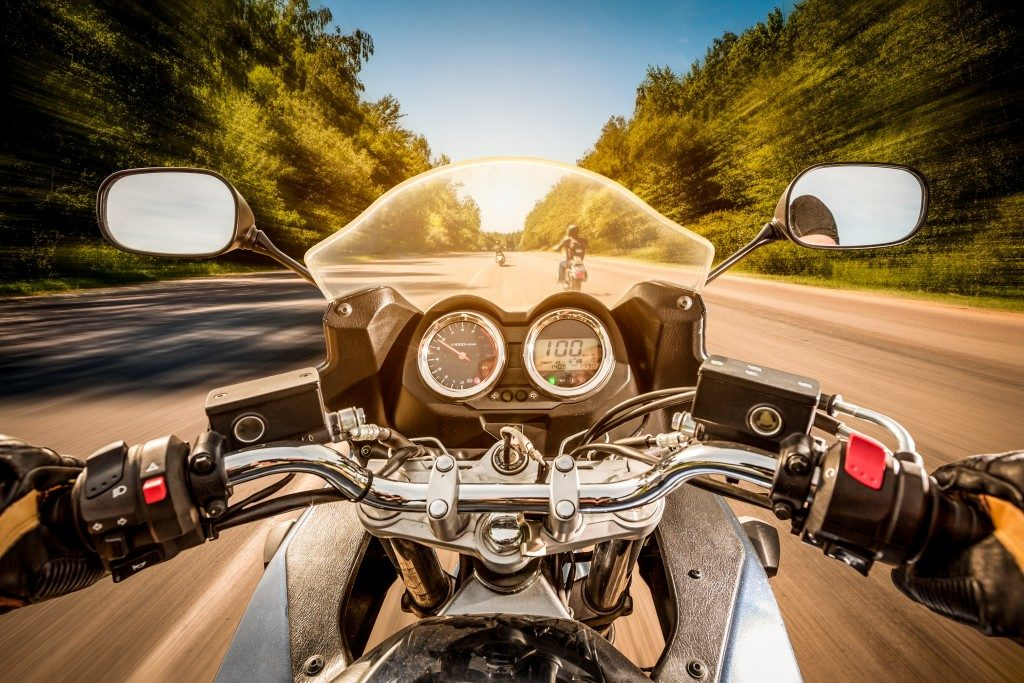 Biker driving a motorcycle rides along the asphalt road
