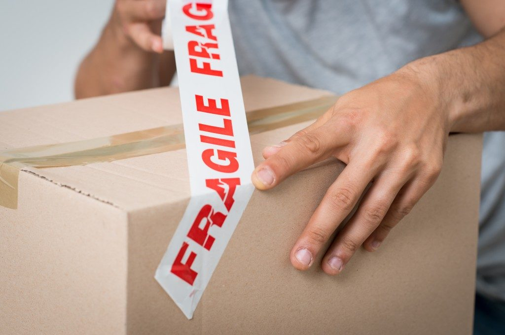 "Box being taped with ""fragile"" sign"