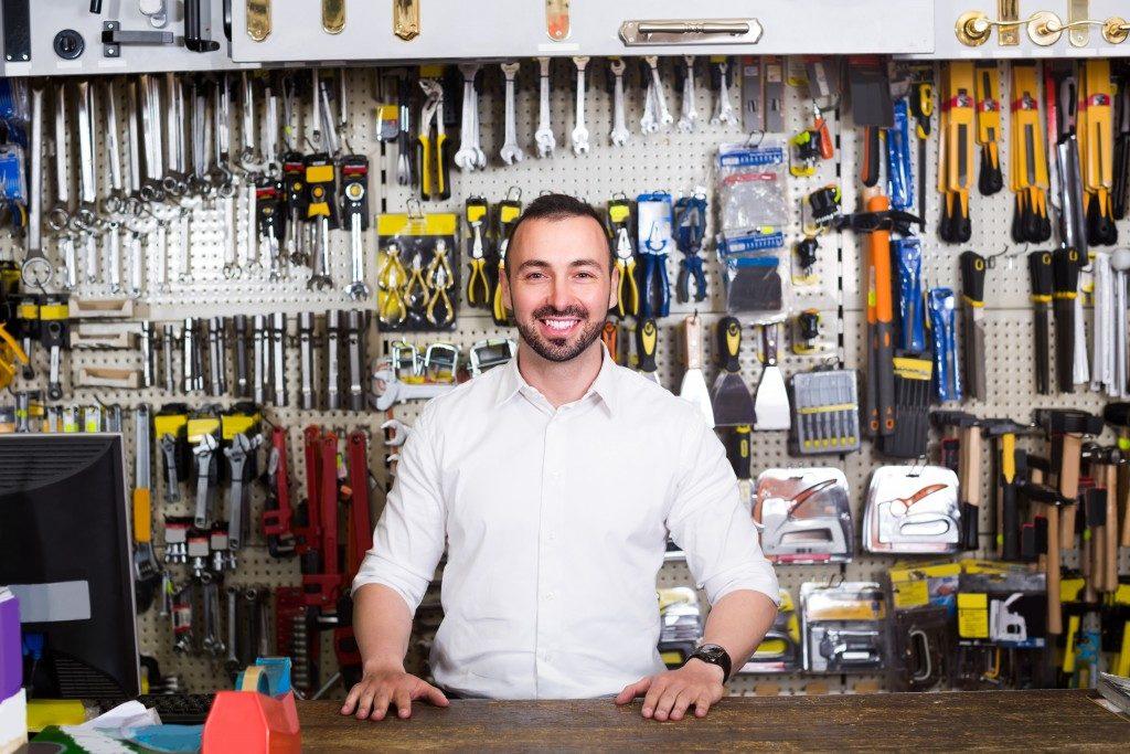 man beside the cash registmachine of hardware store