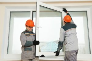 Two male industrial builders workers at window installation