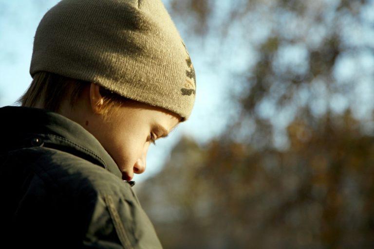Sad boy in autumn warm clothes outdoors
