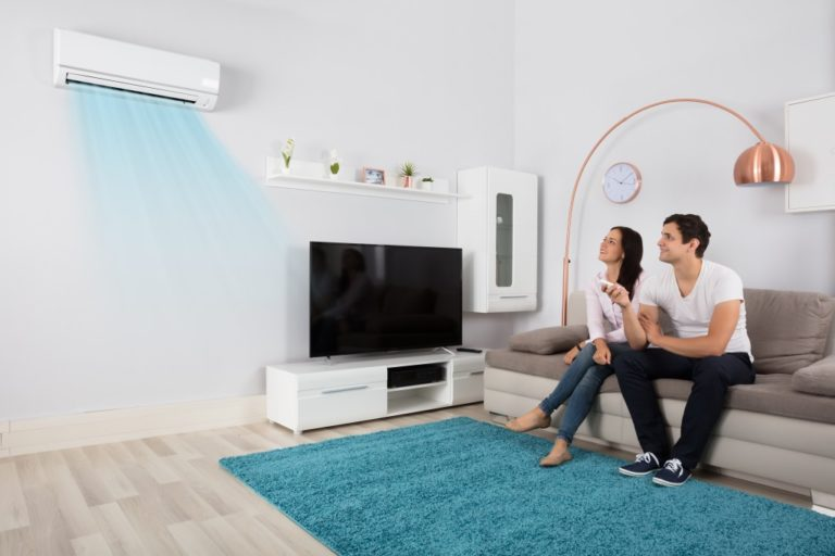 couple in the living room turning the airconditioner