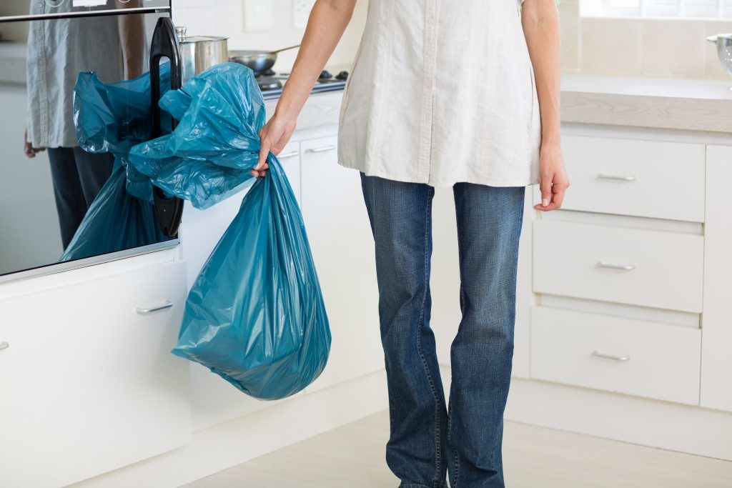 Low section of a young woman carrying garbage bag in the kitchen at house