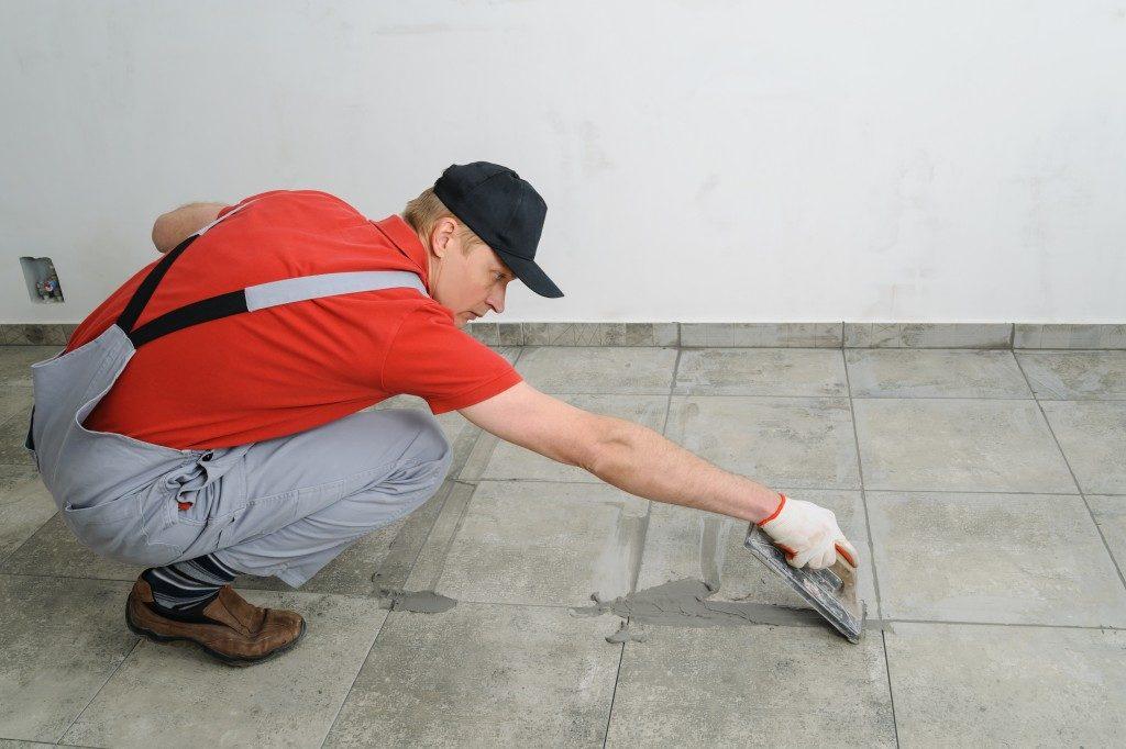 man fixing the floor tiles
