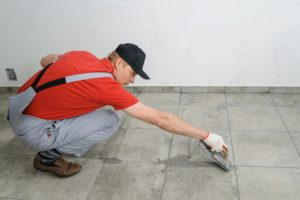 man fixing the floor tiles