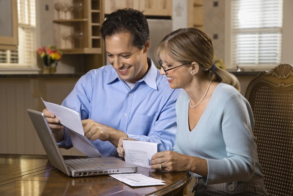 Couple paying bills online with laptop computer at home