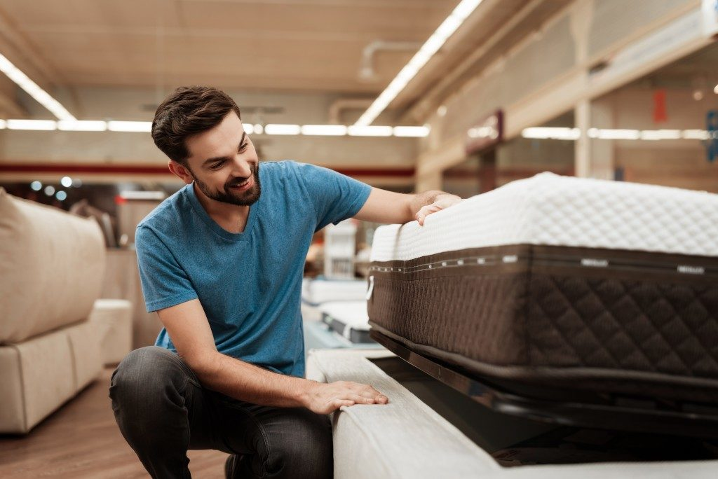 Man looking at mattresses