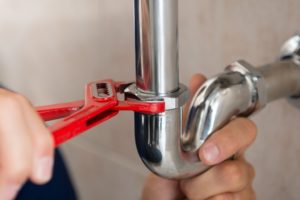 Closeup Of Plumber Fixing Pipe With Wrench