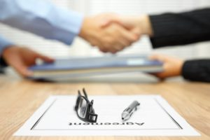 two people shaking hands after agreement