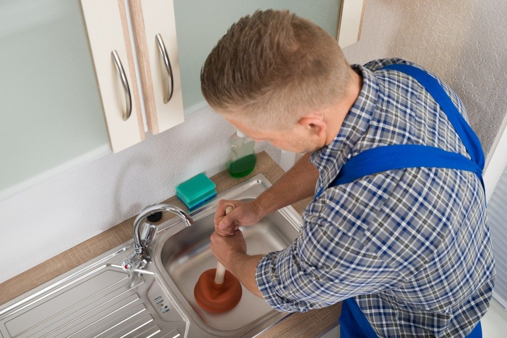 High Angle View Of Worker Pressing Plunger In Steel Kitchen Sink