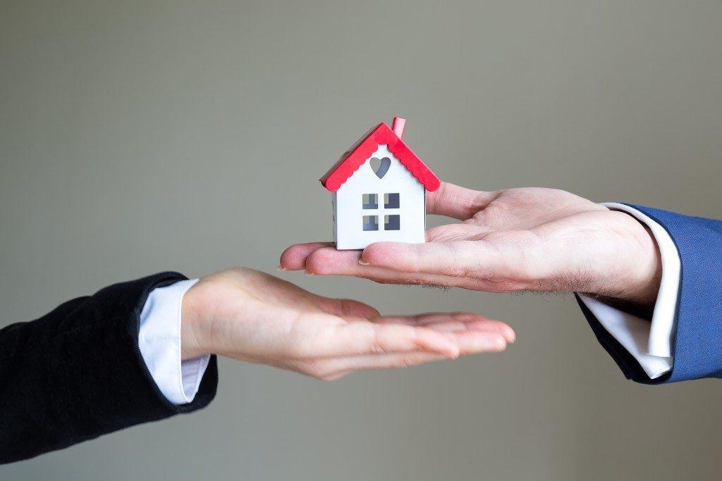 handing over a house model