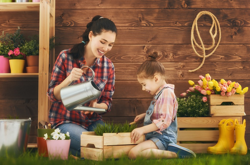 Mother and her daughter engaged in gardening in the backyard