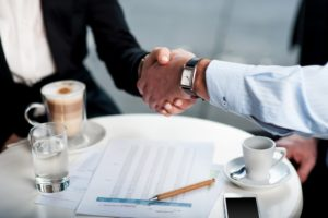 businesspeople shaking hands in an outdoor meeting