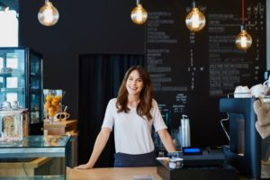 Successful small business owner standing behind the bar