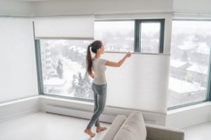 woman adjusting her window blinds