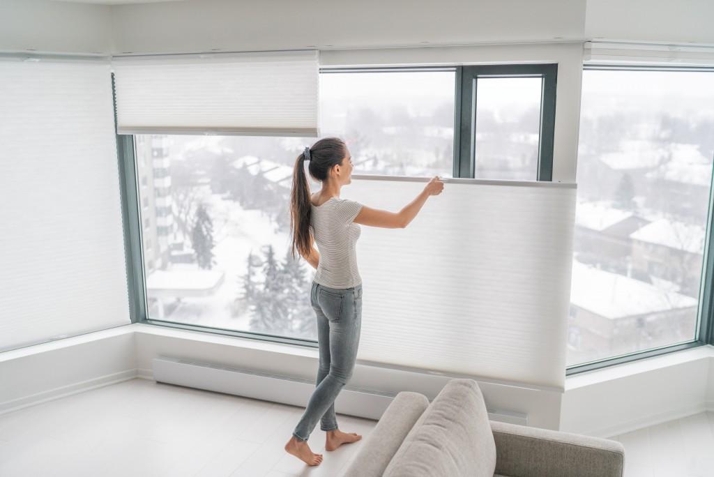 woman adjusting her window blinds