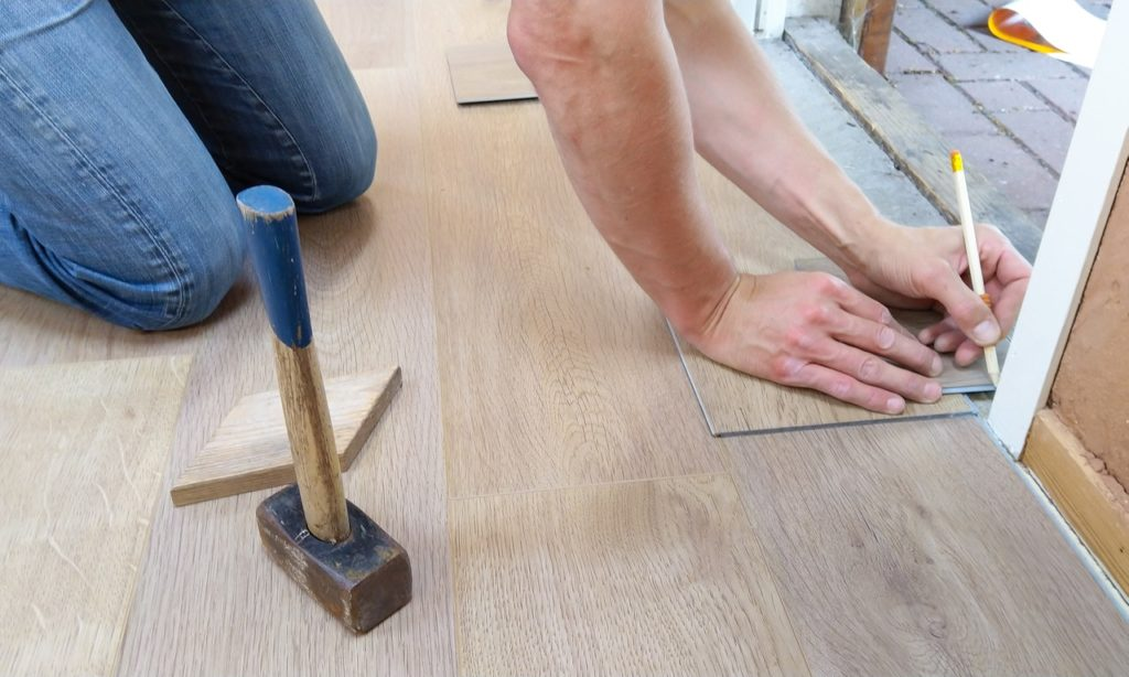 person measuring a tile on the floor